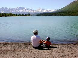 Father and son with bike helmets sitting by a lake