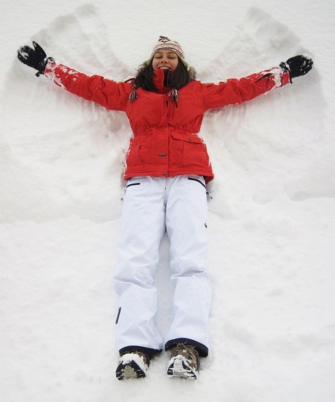 Woman enjoying herself in the snow and doing something for her enjoyment